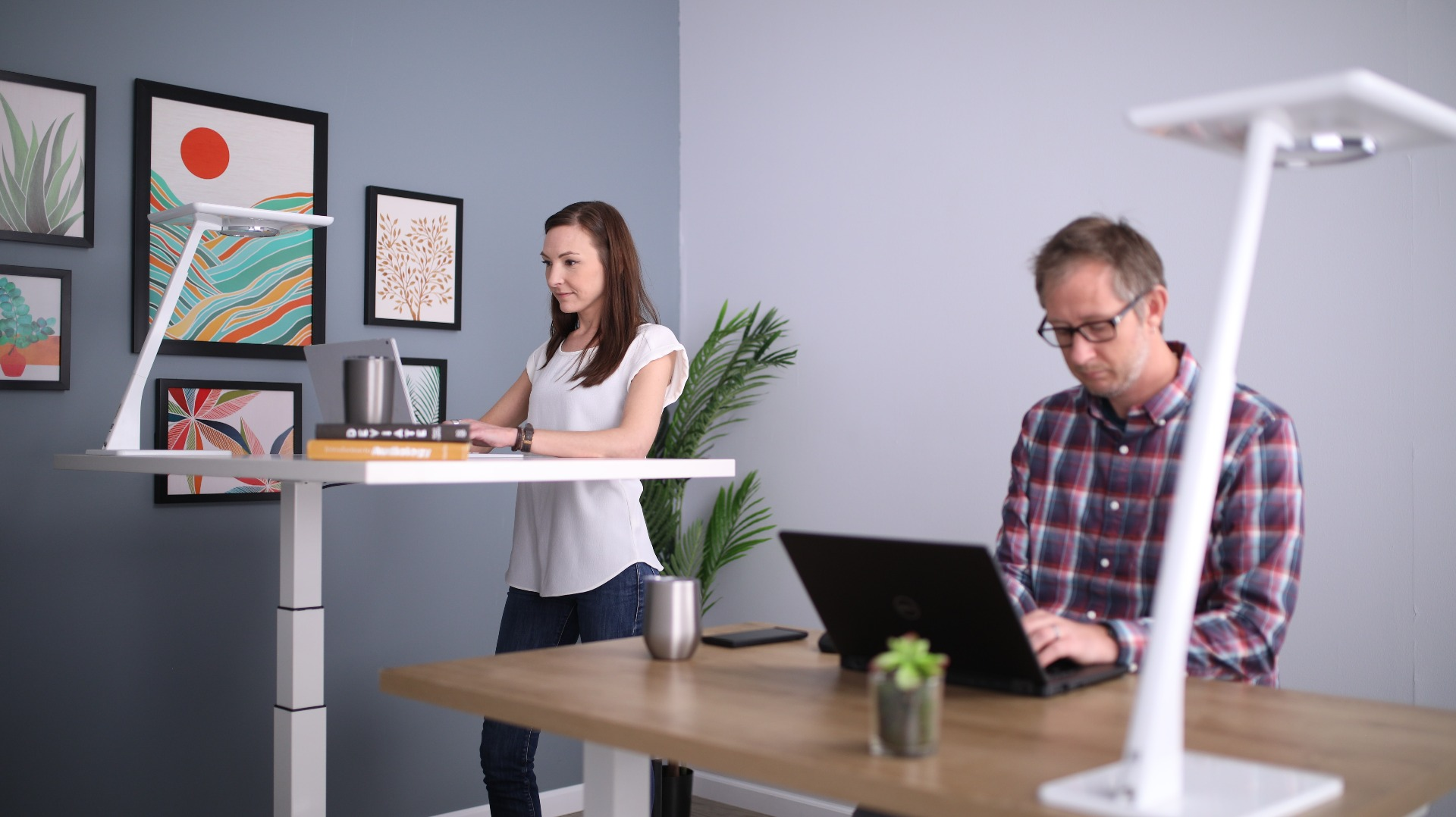 One person sitting, one standing at desks