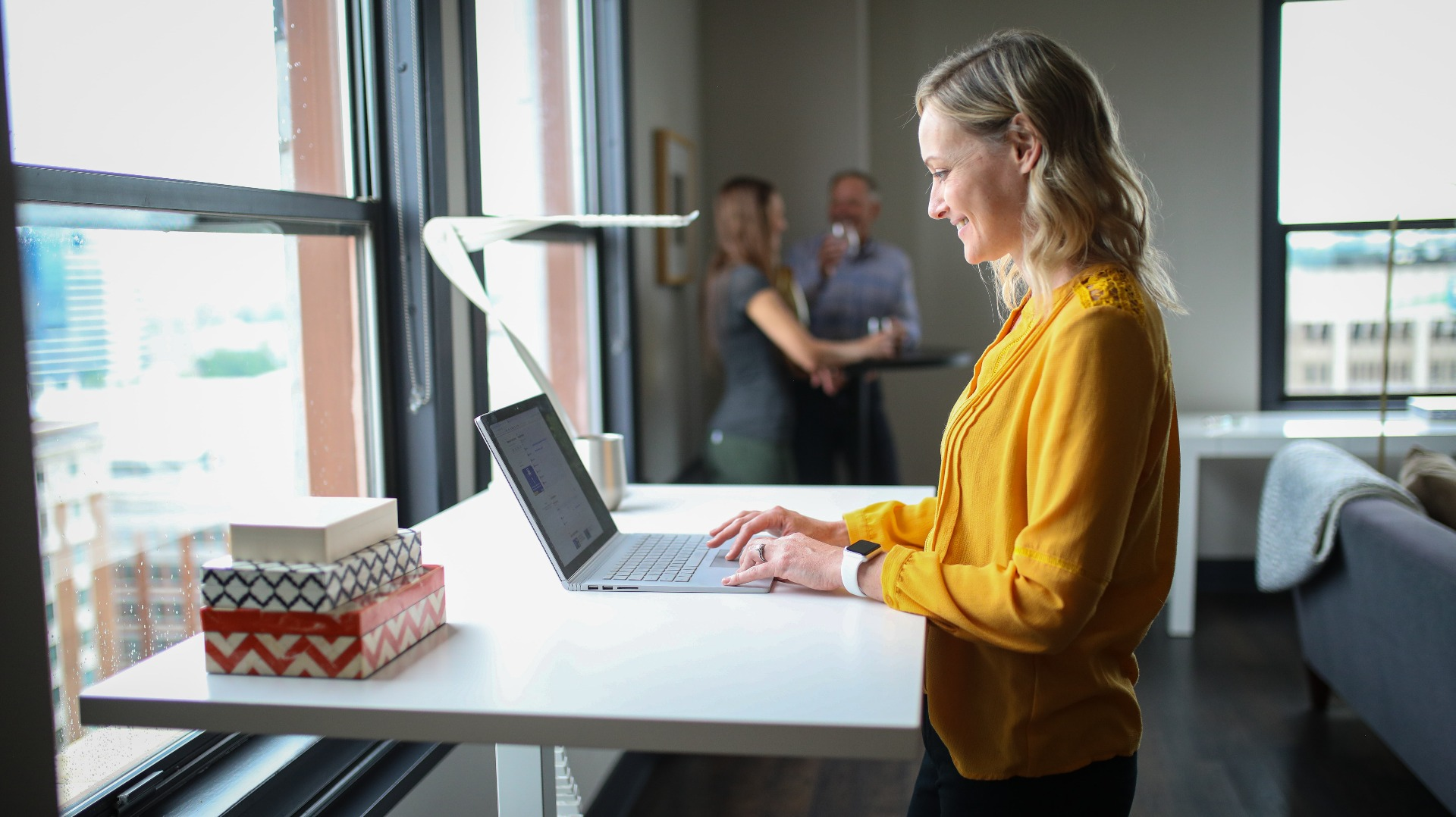 Woman smiling at a standing desk