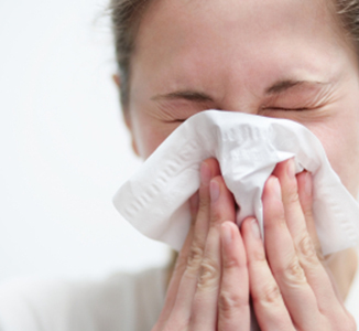 A woman blowing her nose into a paper tissue