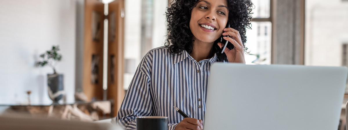 Woman talking on the phone while looking at her laptop