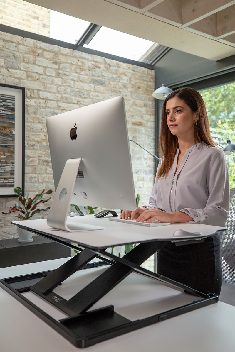 female standing using laptop on top of oploft