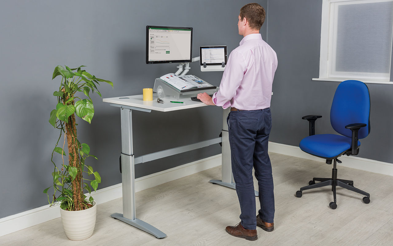 Man standing at sit-stand desk
