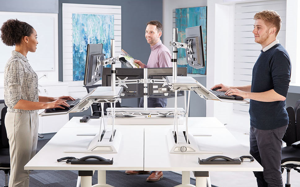 Lifestyle image showing employees using the Lotus Sit-Stand Workstation in an office environment