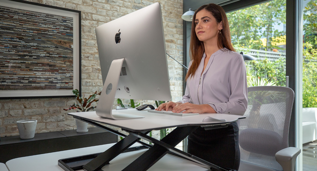 Woman using Oploft Sit-Stand Platform in a standing position