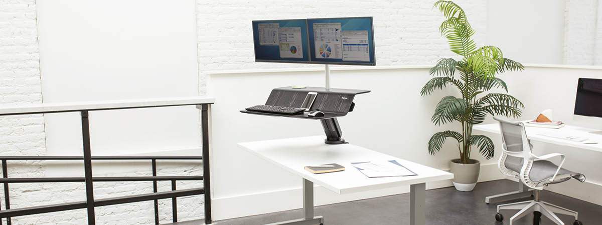 Lifestyle image showing the Lotus™ RT Sit-Stand Workstation attached to a desk within an office environment