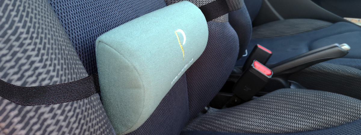 Lifestyle shot showing a lumbar roll being used in the car